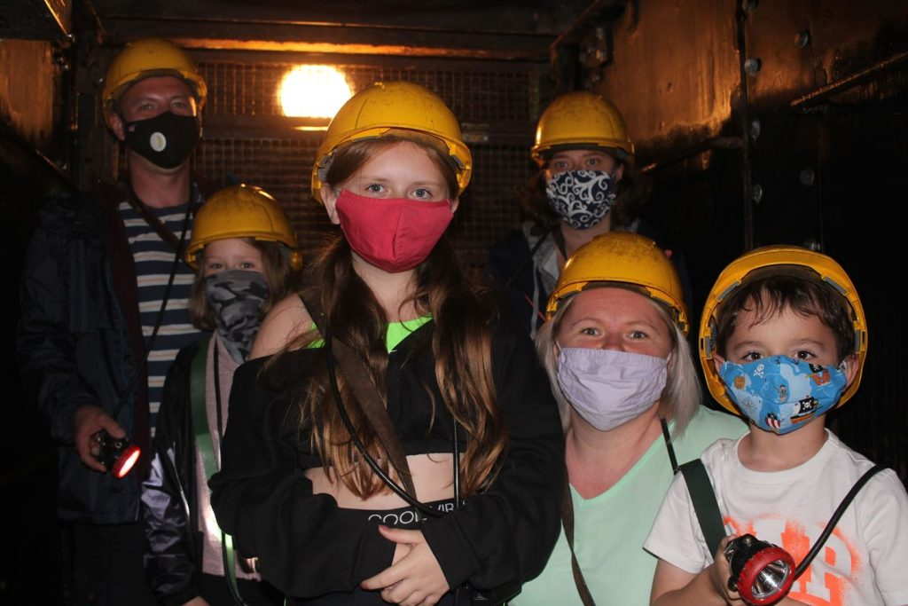 Visitors in the cage wearing masks ready to go underground