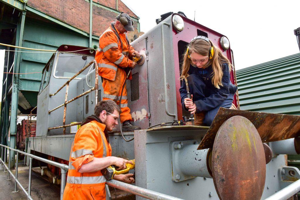 Volunteers restore an old locomotive